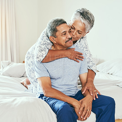Buy stock photo Shot of a cheerful mature man being held by his wife and receiving a kiss on the cheek while they both sit on the bed at home