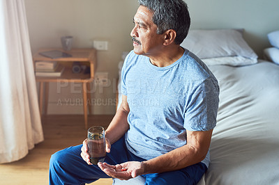 Buy stock photo Shot of a cheerful mature man seated on his bed and about to drink medication with water in the bedroom at home during the day