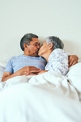 Buy stock photo Shot of a cheerful mature couple relaxing in bed while sharing a kiss at home during the day