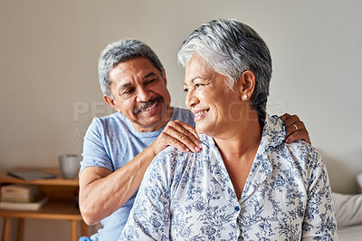 Buy stock photo Shot of a cheerful mature woman receiving a massage on her shoulders by her husband at home during the day