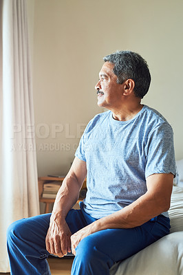 Buy stock photo Shot of a confident mature man looking outside trough his window while contemplating at home during the day