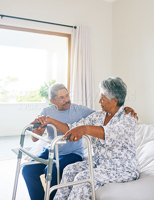 Buy stock photo Shot of a determined mature woman seated on a bed and about to walk with a walking frame while her husband supports her at home