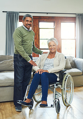 Buy stock photo Portrait of a cheerful elderly woman seated in a wheelchair while being supported and held by her husband inside at home during the day
