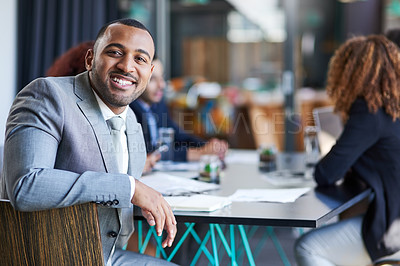 Buy stock photo Portrait of a young businessman sitting in an office with his colleague in the background