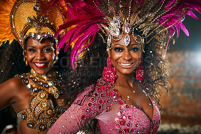 Buy stock photo Cropped portrait of two beautiful samba dancers performing in a carnival with their band