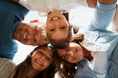 Buy stock photo Low angle portrait of a young family of four standing around in a huddle