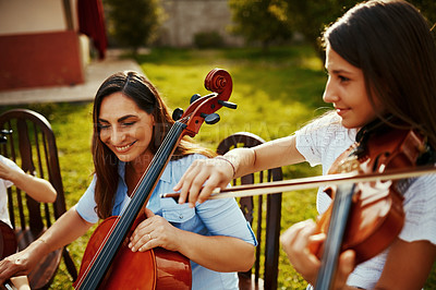 Buy stock photo Cropped shot of a beautiful mother playing instruments with her adorable daughter outdoors