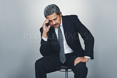 Buy stock photo Studio shot of a mature businessman looking stressed out against a grey background