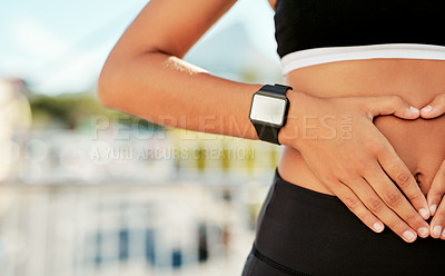 Buy stock photo Closeup shot of an unrecognizable woman making a heart shape over her stomach outdoors