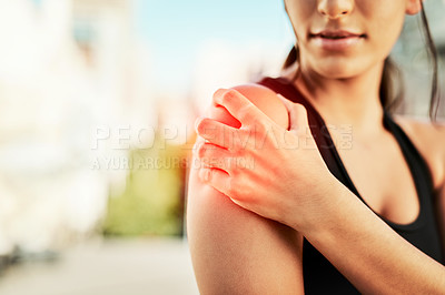 Buy stock photo Closeup shot of a sporty young woman holding her shoulder in pain while exercising outdoors