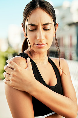 Buy stock photo Shot of a sporty young woman holding her shoulder in pain while exercising outdoors