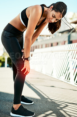 Buy stock photo Shot of a sporty young woman holding her knee in pain while exercising outdoors