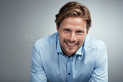 Buy stock photo Studio portrait of a handsome young businessman posing against a grey background