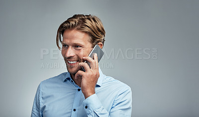 Buy stock photo Studio shot of a handsome young businessman talking on a cellphone against a grey background