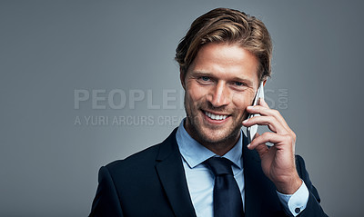 Buy stock photo Studio portrait of a handsome young businessman talking on a cellphone against a grey background