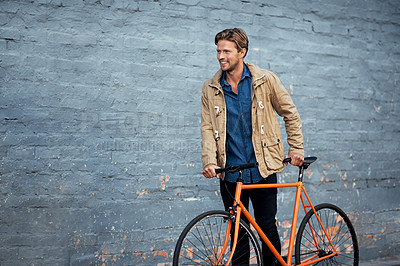 Buy stock photo Cropped shot of a handsome young man standing with his bike against a grey brick wall