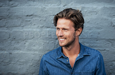 Buy stock photo Cropped shot of a handsome young man standing against a grey brick wall