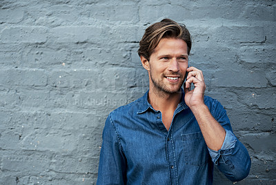 Buy stock photo Cropped shot of a handsome young man using his cellphone while standing against a grey brick wall