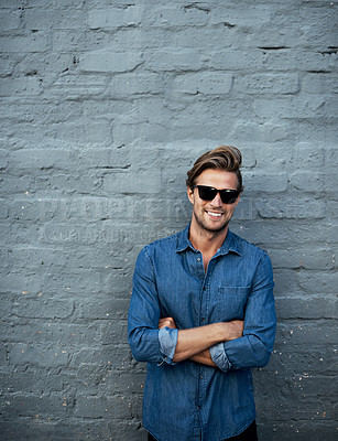 Buy stock photo Cropped portrait of a handsome young man standing with his arms folded against a grey brick wall