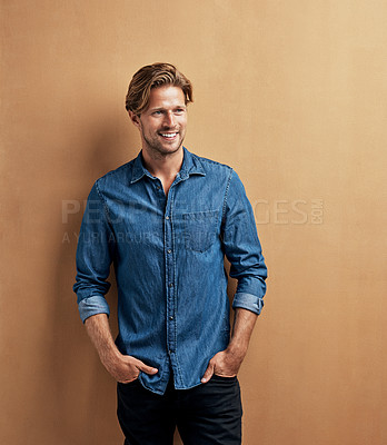 Buy stock photo Studio shot of a handsome young man standing with his hands in his pockets against a bronze background