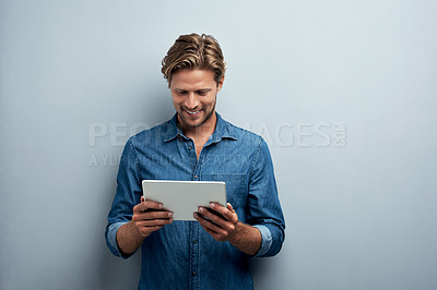Buy stock photo Studio shot of a handsome young man using his tablet while standing against a grey background