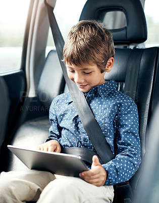 Buy stock photo Shot of an adorable little boy using a digital tablet in the backseat of a car