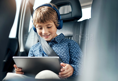 Buy stock photo Shot of an adorable little boy using a digital tablet and headphones in the backseat of a car