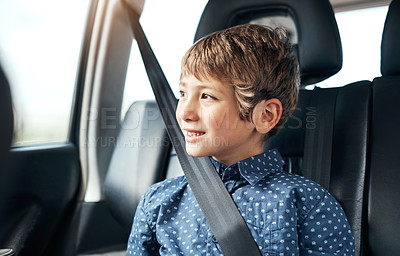 Buy stock photo Shot of an adorable little boy traveling in the backseat of a car and looking out the window