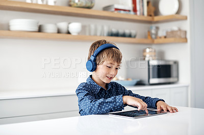 Buy stock photo Shot of an adorable little boy wearing headphones while using a digital tablet at home