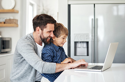 Buy stock photo Shot of a father and his little son using a laptop together at home