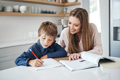 Buy stock photo Shot of a young woman helping her adorable son with his schoolwork at home