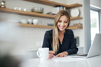 Buy stock photo Shot of an attractive young woman using a laptop and going through paperwork at home