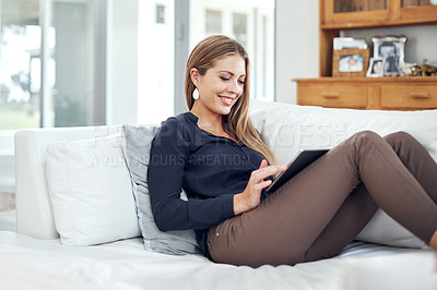 Buy stock photo Shot of an attractive young woman using a digital tablet on the sofa at home