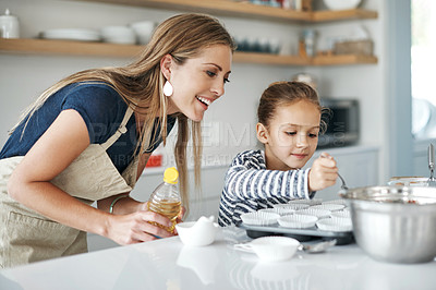 Buy stock photo Shot of an adorable little girl baking with her beautiful mother in the kitchen at home