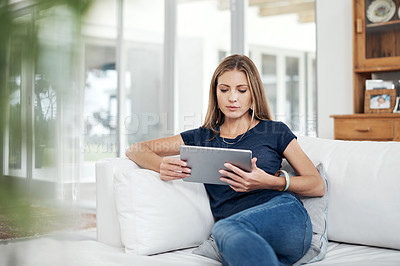 Buy stock photo Cropped shot of a beautiful young woman using a tablet on the sofa in the living room at home