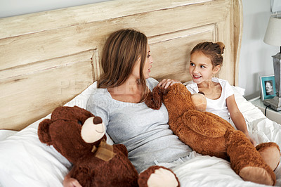 Buy stock photo Shot of an adorable little girl lying in bed with her beautiful mother at home