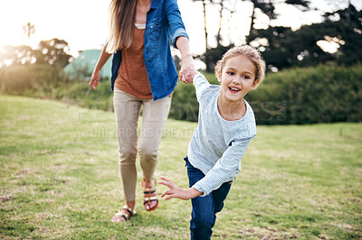 Buy stock photo Shot of an adorable little girl holding her unrecognizable mother's hand outdoors