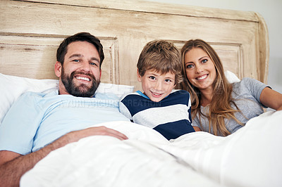Buy stock photo Portrait of a happy family bonding in bed at home