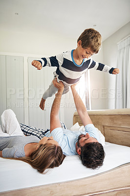 Buy stock photo Shot of a happy family having fun in bed at home