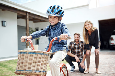 Buy stock photo Shot of a little boy riding a bicycle while his parents watch in the background