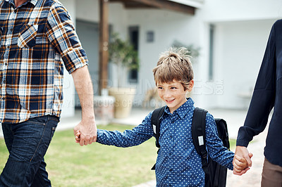 Buy stock photo Shot of an adorable little boy wearing a backpack while walking with his parents outdoors