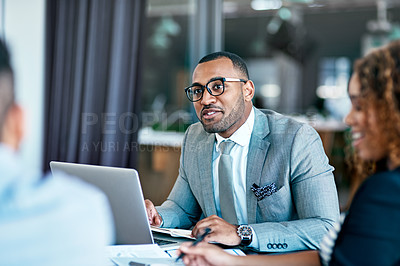Buy stock photo Cropped shot of a handsome young businessman working on his laptop during a meeting in the boardroom