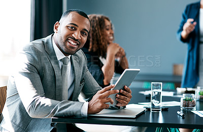 Buy stock photo Cropped portrait of a handsome young businessman working on his tablet during a meeting in the boardroom