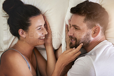 Buy stock photo Cropped shot of a young attractive couple lying in bed together at home