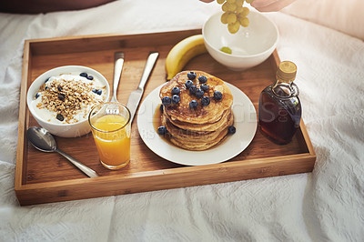 Buy stock photo High angle shot of an unrecognizable man enjoying breakfast in bed at home