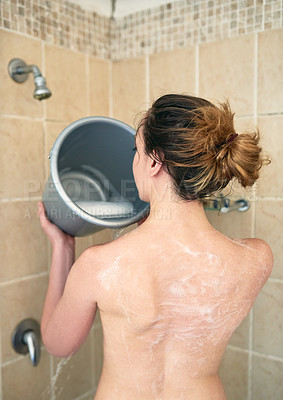 Buy stock photo Rearview shot of an unrecognizable woman washing her body with a bucket of water in the bathroom at home