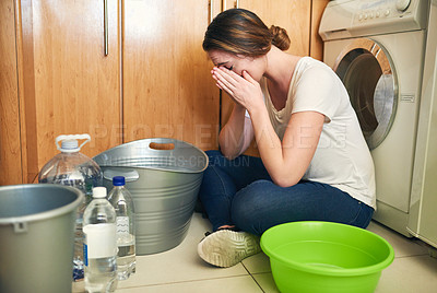 Buy stock photo Shot of a beautiful young woman crying on the floor in the kitchen at home
