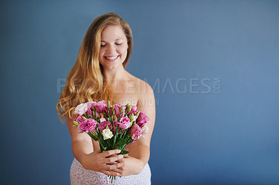 Buy stock photo Studio shot of a cheerful young woman holding a bouquet of flowers while standing in her underwear against a blue background