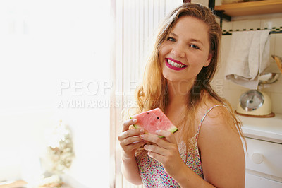 Buy stock photo Portrait of a cheerful young woman enjoying a slice of watermelon while being seated on a chair in the kitchen at home