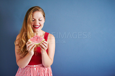 Buy stock photo Cropped shot of a beautiful young woman posing with a watermelon against a blue wall indoors